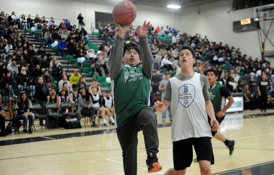 Luis Rivera, left, of Pacifica High scores against Josh Jones, of Buena High at the Pacifica High School gym. The Unified Sports Champions teams, a Special Olympics program, faced off in a recent basketball game.