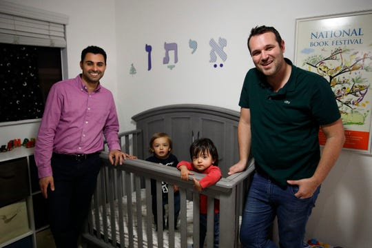 In this Jan. 23, 2018, photo, Elad Dvash-Banks, left, and his partner, Andrew, pose for photos with their twin sons, Ethan, center right, and Aiden in their apartment in Los Angeles.  The U.S. government had only granted citizenship to one of the boys, but a judge overruled that.