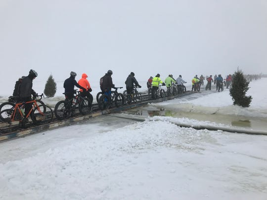 Cyclists cross a bridge installed on Lake Winnebago by the Paynes Point Hook & Spear Club. The club plows a route across the ice for sturgeon spearing season. Cyclists are welcome to use it for the ride organized by Fox Cities Cycling Association.
