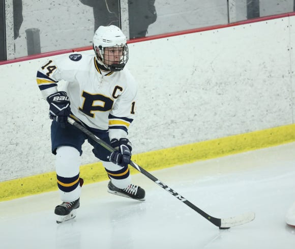 Pelham's Connor Evans (14) looks to make a play from behind the goal in the division II semifinal ice hockey game at the Ice Hutch in Mount Vernon on Thursday, February 21, 2019.