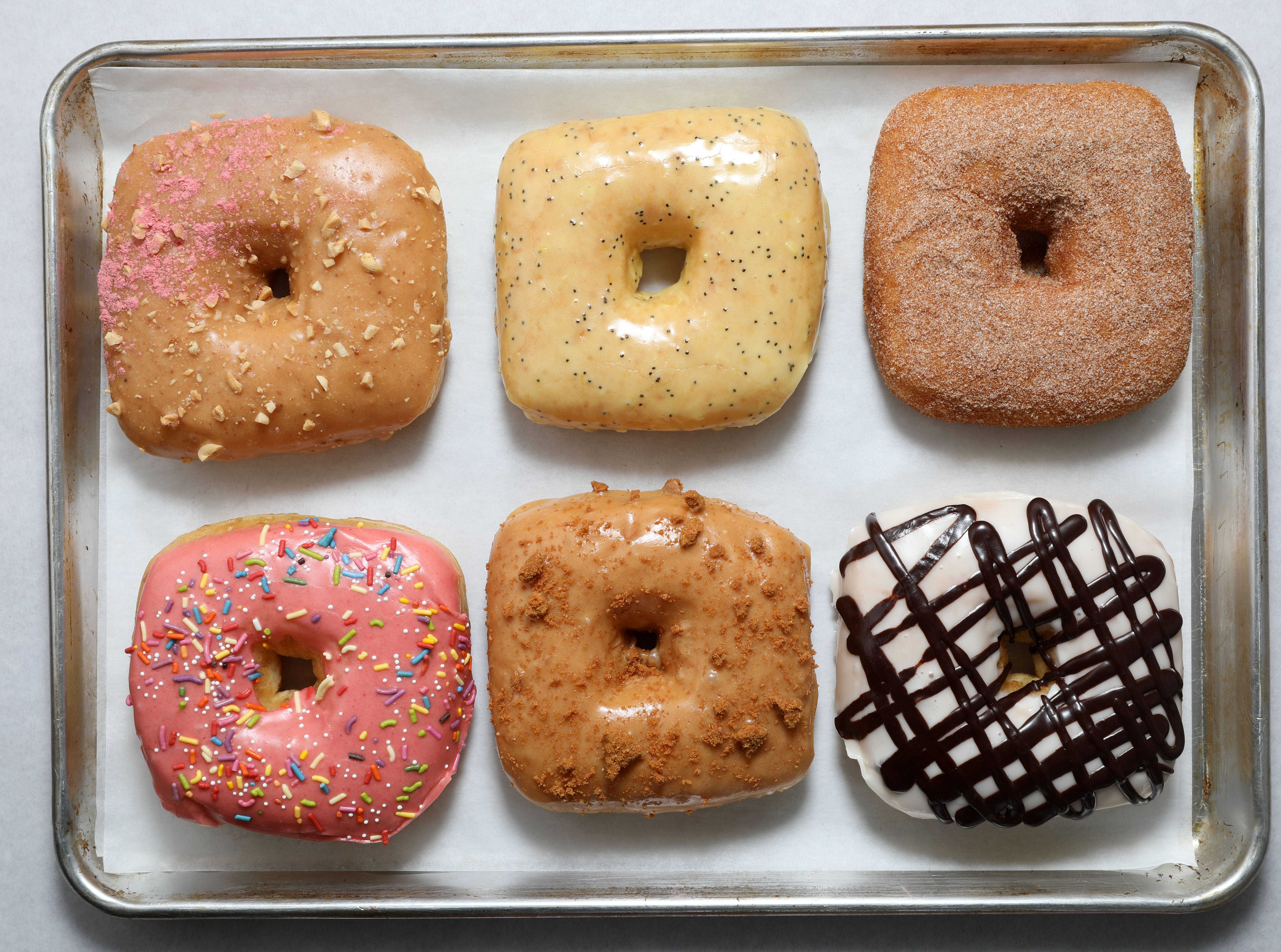 An assortment of vegan doughnuts by Peaceful Provisions Feb. 18, 2019 in Tarrytown. Top row from left: peanut butter with roasted peanuts and strawberry powder, lemon poppy seed glaze, cinnamon sugar. Bottom row from left: strawberry glaze with sprinkles, cookie butter icing with cookie crumble, vanilla glaze with chocolate marble.