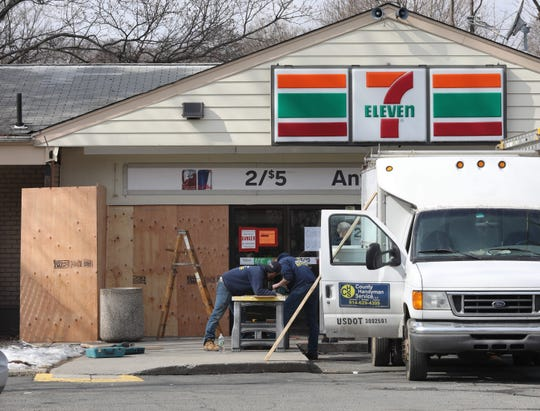 Workers with County Handyman Service, LLC. cut plywood to further secure the broken window area of the 7-Eleven on North Central Highway in Haverstraw, Feb. 22, 2019.