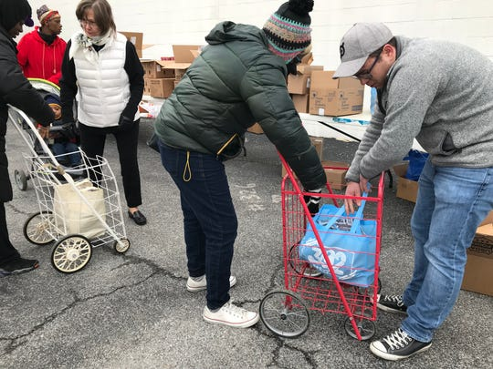 Volunteers pass out food from the Food Bank of Delaware to food stamps recipients who are awaiting their next payment