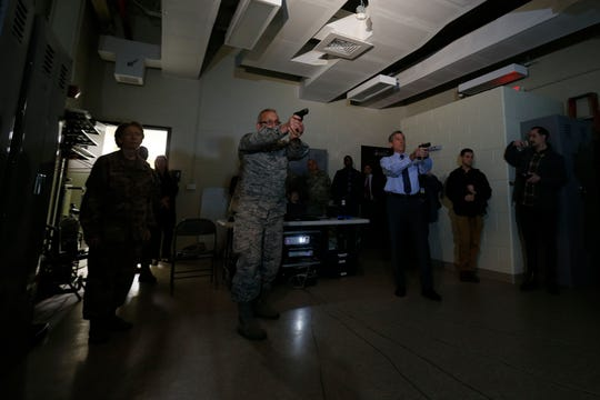 Gov. John Carney, right, and Master Sgt. Randy Fisher go through simulations during firearms training while touring the Delaware National Guard Counterdrug Task Force facilities Friday.