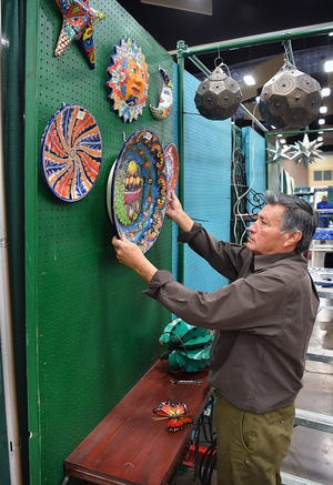 Saul Ramos, Sr. hangs up hand painted Talavera pottery as he prepares his Old World Pottery booth for the Arts Alive! Home and Garden Festival 2019 at the Ray Clymer Exhibit Hall.