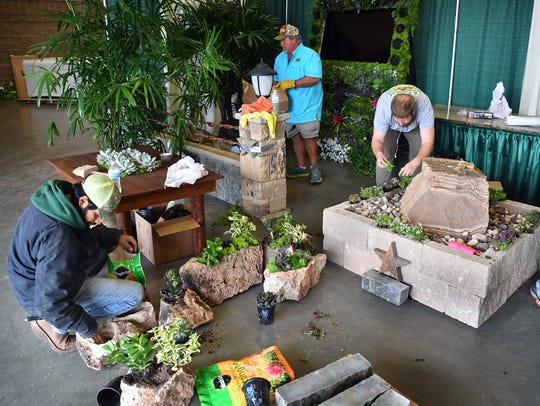 Longo Landscape Stone and Brick workers arrange natural greenery and small plants while setting up their Arts Alive! Home and Garden Festival area Friday morning at the Ray Clymer Exhibit Hall.
