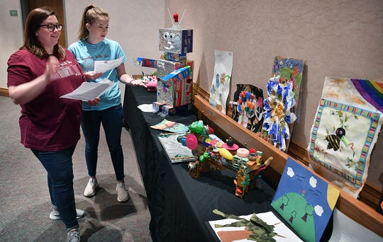 Lauren McKechnie, left, and Morgan Lord of Texoma Community Credit Union look over entries in the first Youth Recycled Art Contest at the Arts Alive! Home and Garden Festival Friday. K-12 students created paintings, collage and sculpture using recycled materials.
