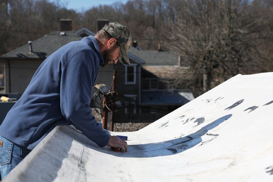 Robby Frame of the Muskingum County Maintenance Department, patches the roof of the Family and Children First building on Putnam Avenue recently.