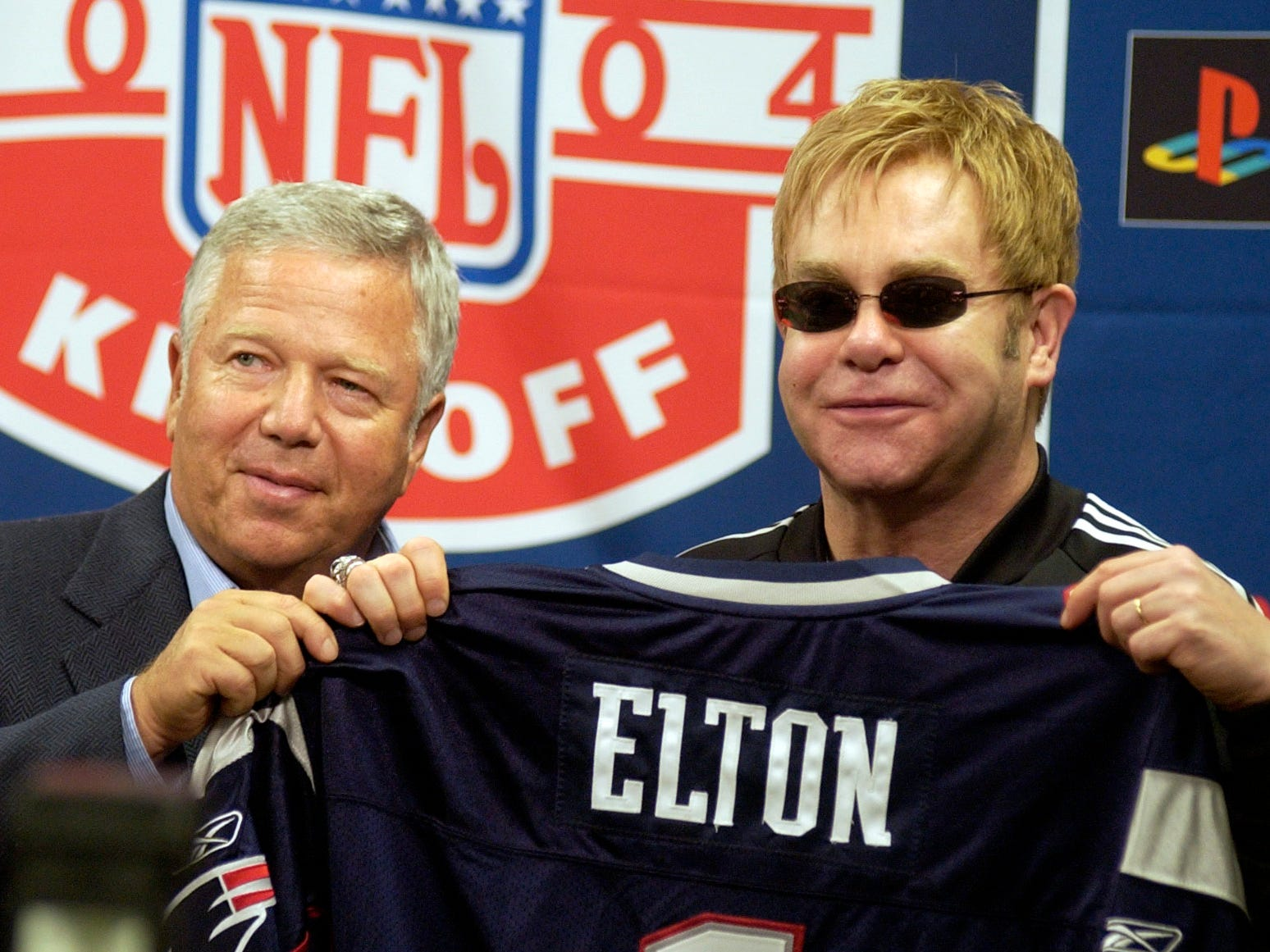Kraft gives entertainer Elton John a Patriots jersey before the opening day of the 2004 NFL season.