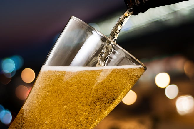 A glass of beer being poured. =