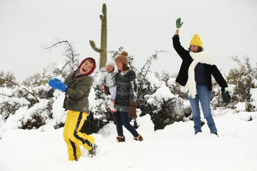 Braylen Lentine, his mom Adianne holding  Georgia and grandmother Ava Dahl have a snowball fight after a winter storm brought six inches of snow to the Scottsdale, Ariz. area. Feb. 22,2019.