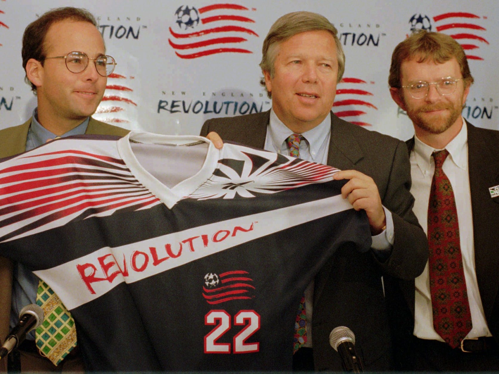 "Owner of the Major League Soccer team New England Revolution, Kraft and his son Jonathan, left, hold up a new design for the team jersey as ""Revolution"" manager Brian O'Donovan, right, looks on at a news conference at Foxboro Stadium."