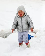 Two year old Georgia Lentine cries during her first experience with snow after a winter storm brought six inches of snow to the Scottsdale, Ariz. area. Feb. 22,2019.