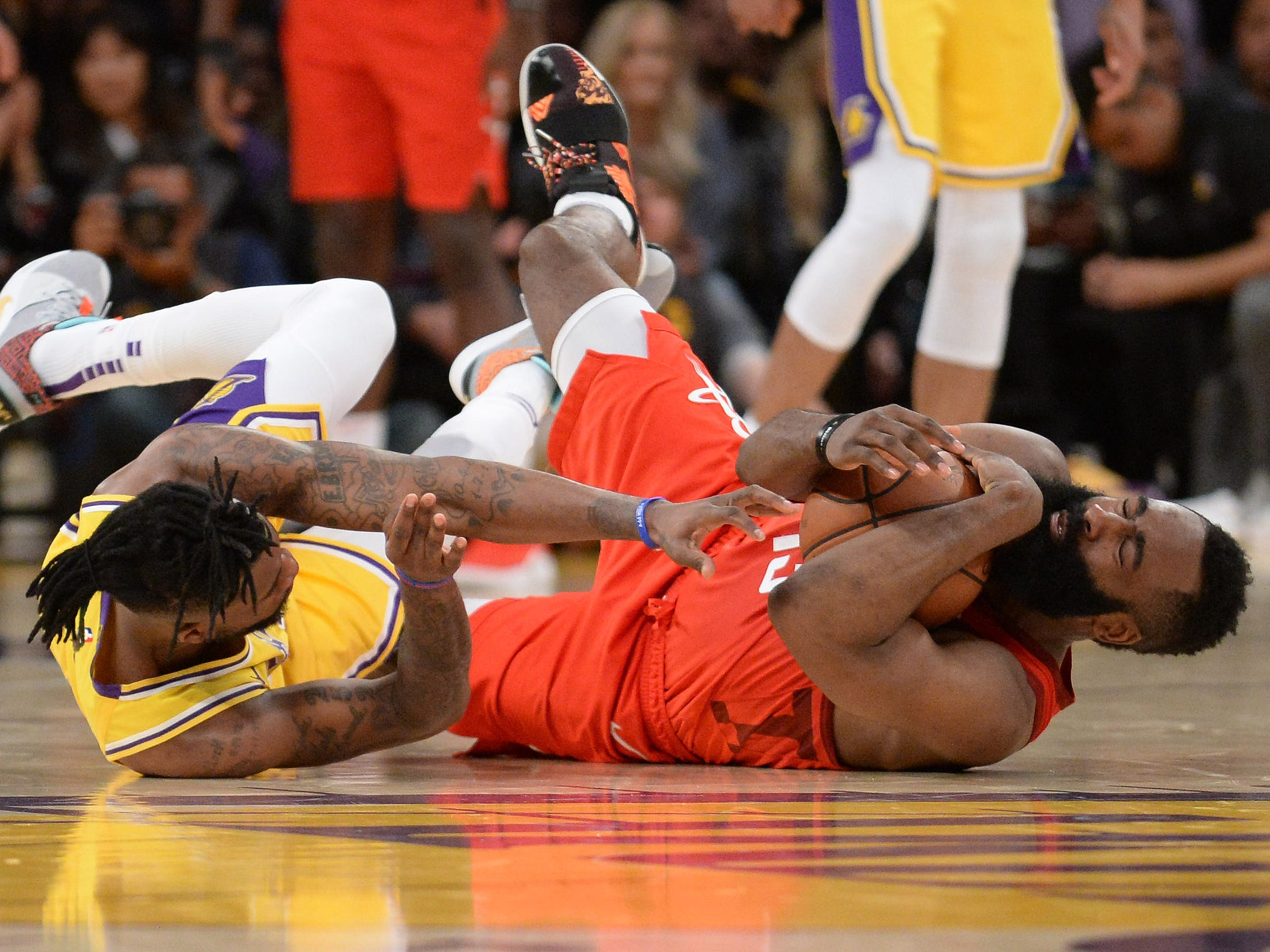 Feb. 21: Rockets guard James Harden (13) hits the deck to corral a loose ball against Lakers guard Reggie Bullock (35) during the second half in Los Angeles.