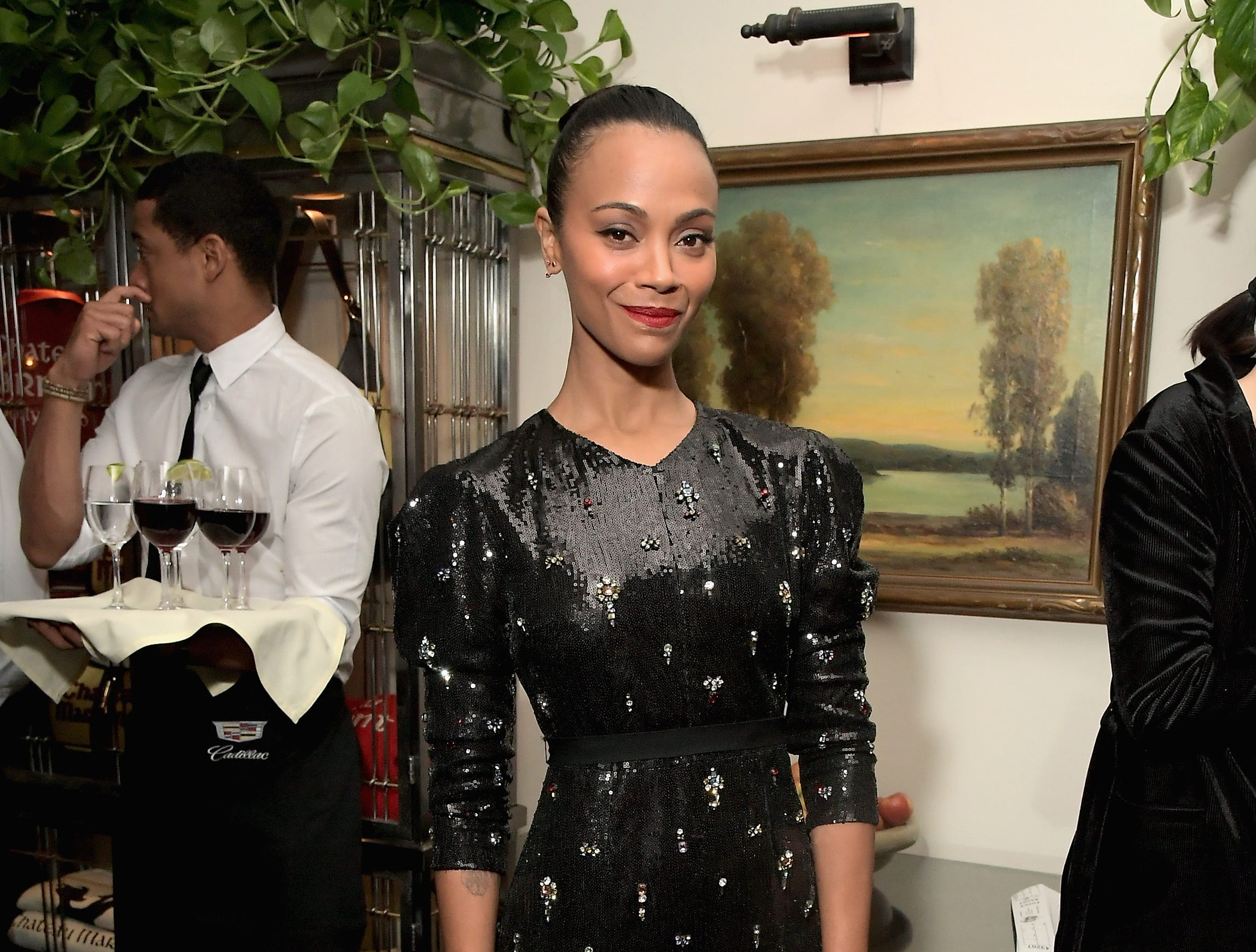 Zoe Saldana stands in front of a wonderful nature water color painting at the Cadillac Oscar Week Celebration.