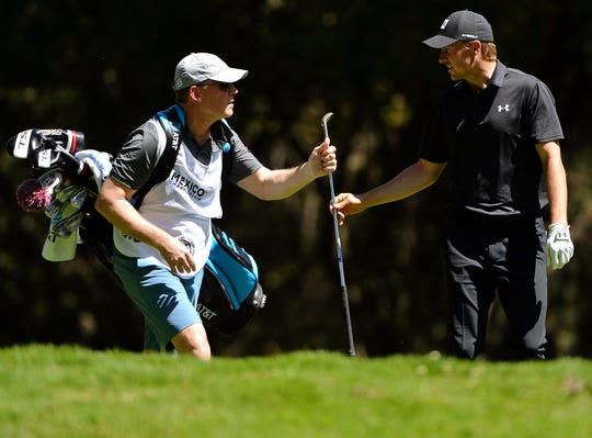 Jordan Spieth hands his club to his father (and caddie), Shawn Spieth, on during the first round of the WGC - Mexico Championship.