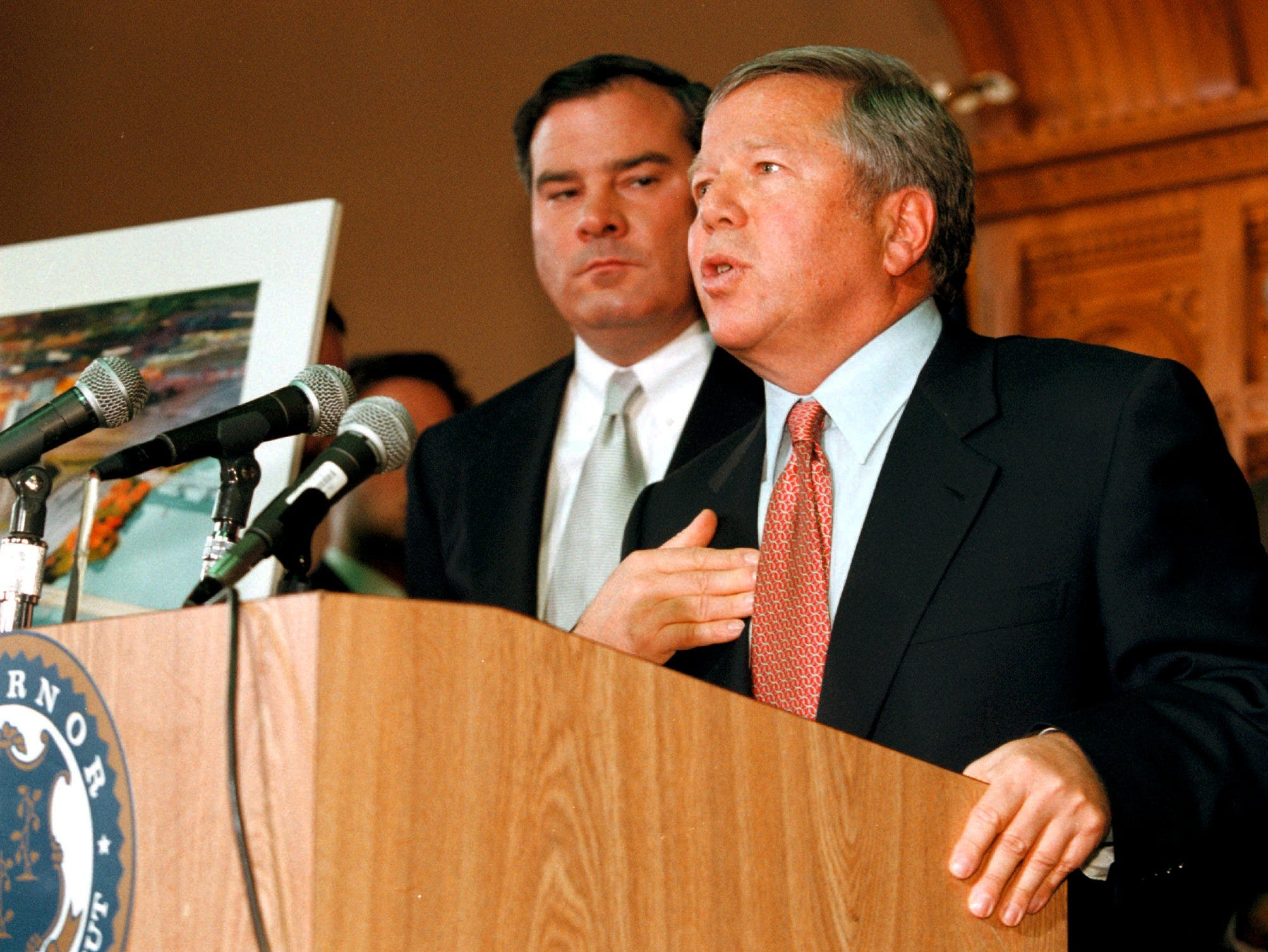 Kraft speaks as Governor of Connecticut John Rowland looks on during the announcement of the NFL football team moving to the city of Hartford at the State Capitol building.