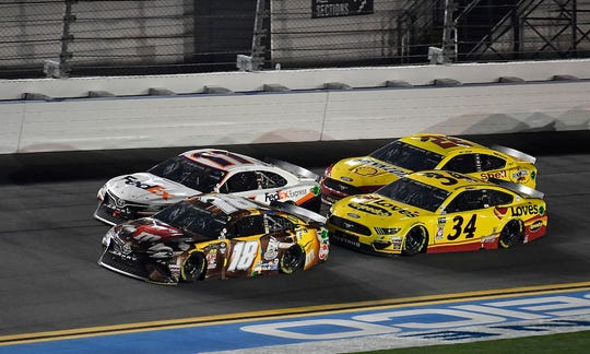 Ford drivers Joey Logano (22) and Michael McDowell (34) race agianst Toyota drivers Denny Hamlin (11) and Kyle Busch (18) during the closing laps of the 2019 Daytona 500.
