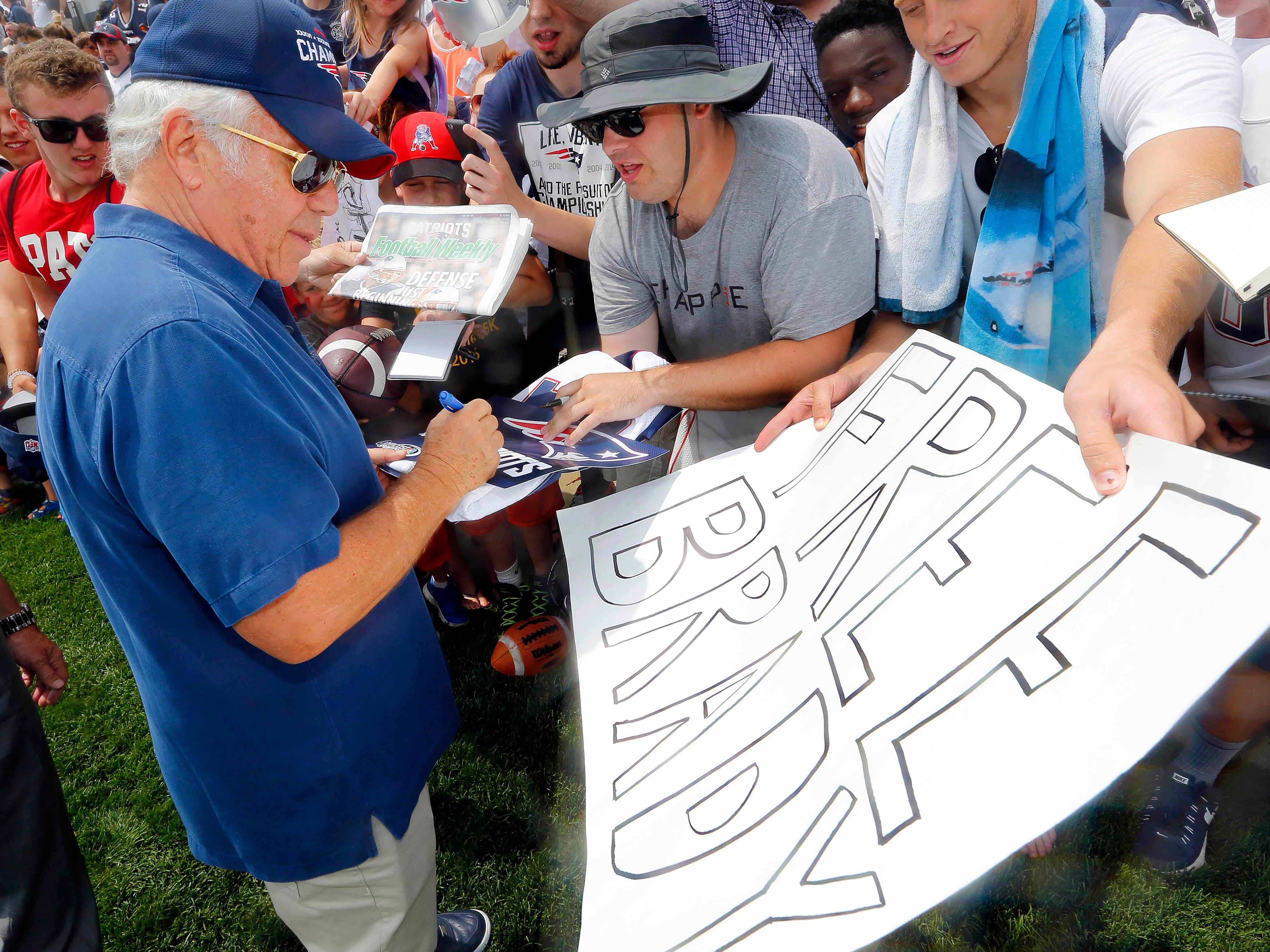 Kraft signs autographs during training camp at Gillette Stadium.