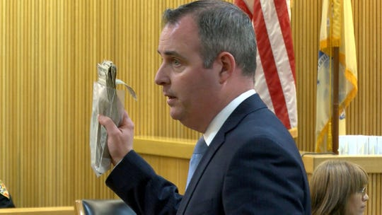 Monmouth County Assistant Prosecutor Chris Decker holds up some of the money that the State believes was stolen from Sarah Stern after she was killed by Liam McAtasney.   He is on trial for the murder of Sarah Stern Friday, February 22, 2019. .
