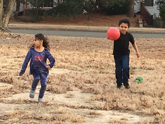 8-year-old Kane Hicks (right) and 6-year-old Jahmadi Hicks play with a ball in their family's yard in Neptune.