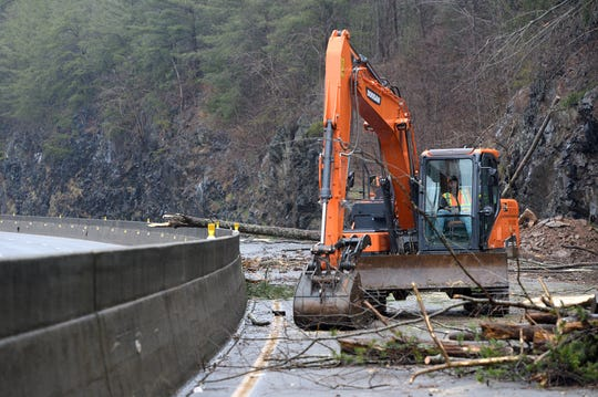 Workers use chainsaws and large machinery to clear I-40 at mile marker 7.5 of debris from a Friday night rockslide on Feb. 23, 2019.