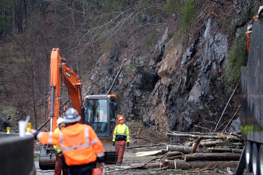 Workers use chain saws and large machinery to clear Interstate 40 at mile marker 7.5 of debris from a rock slide on Feb. 23, 2019.