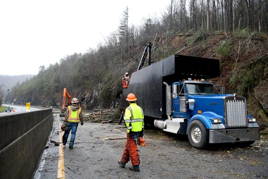 Workers use chainsaws and large machinery to clear I-40 at mile marker 7.5 of debris from a Friday night rockslide on Feb. 23, 2019. The NC Department of Transportation expects the highway to be closed for a week as they clean up and stabilize the area which still had falling trees and rocks Saturday afternoon.