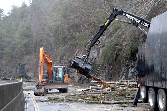 Workers use chainsaws and large machinery to clear I-40 at mile marker 7.5 of debris from a rockslide on Feb. 23, 2019.