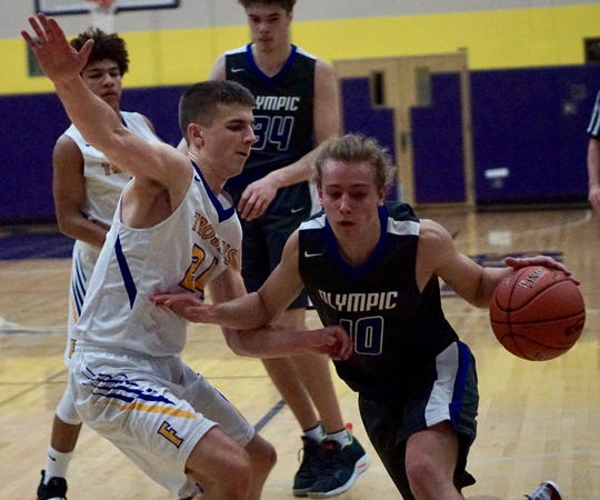 Olympic's Brady Nelson tries to dribble past Fife's defense during Saturday's regional basketball game.