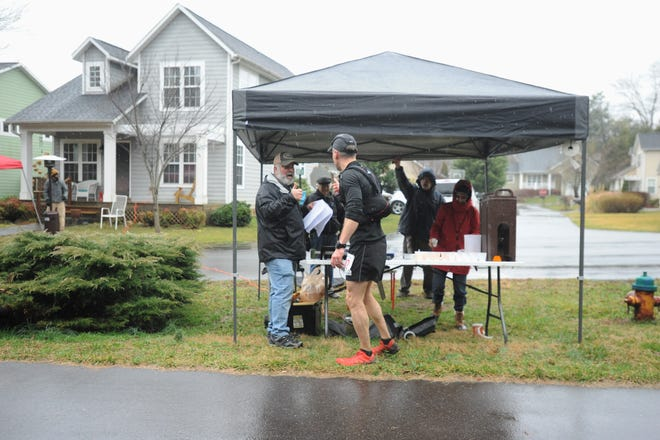 A runner stops for a drink and thanks community members for supporting him, as he approaches the finish line of the Black Mountain Marathon on Feb. 23.