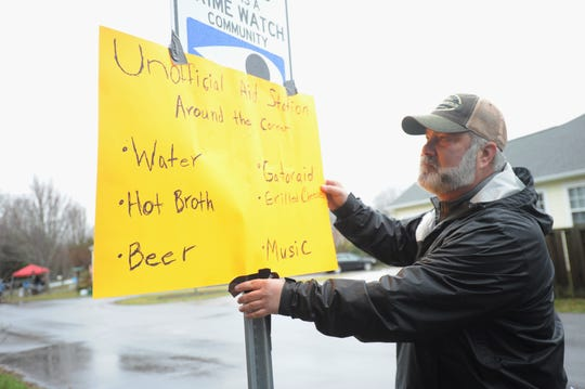 """Chris Maloney hangs a sign for an """"unofficial aid station"""" in the Cotton Creek community on Feb. 23, as dozens of locals gathered to cheer on runners in the Mount Mitchell Challenge and Black Mountain Marathon."""