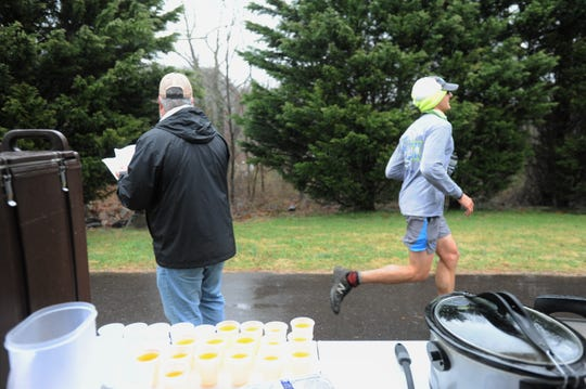 """A Black Mountain Marathon runner makes his way past the """"unofficial aid station"""" in a neighborhood along the Flat Creek Greenway."""