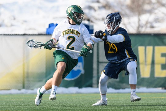 Vermont's Jack Knight (2) runs past Quinnipiac's Nick Mascetti (29) with the ball during the men's lacrosse game between the Quinnipiac Bobcats and the Vermont Catamounts at Virtue Field on Saturday afternoon February 23, 2019 in Burlington, Vermont.