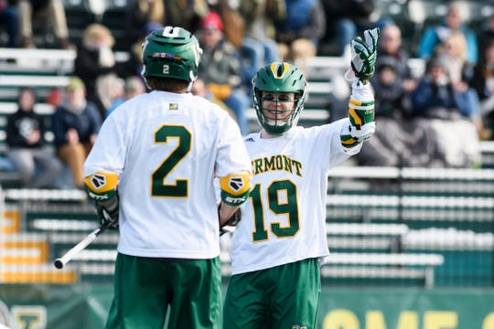 Vermont's Braiden Davis (19) and Jack Knight (2) celebrate a goal during the men's lacrosse game between the Quinnipiac Bobcats and the Vermont Catamounts at Virtue Field on Saturday afternoon February 23, 2019 in Burlington, Vermont.