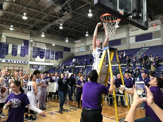 Mason's McKenzie Cano cuts a piece of the net at San Marcos High School's Snake Pit after the Cowgirls beat San Saba 46-36 in the Region IV-2A championship game, Saturday, February 23, 2019