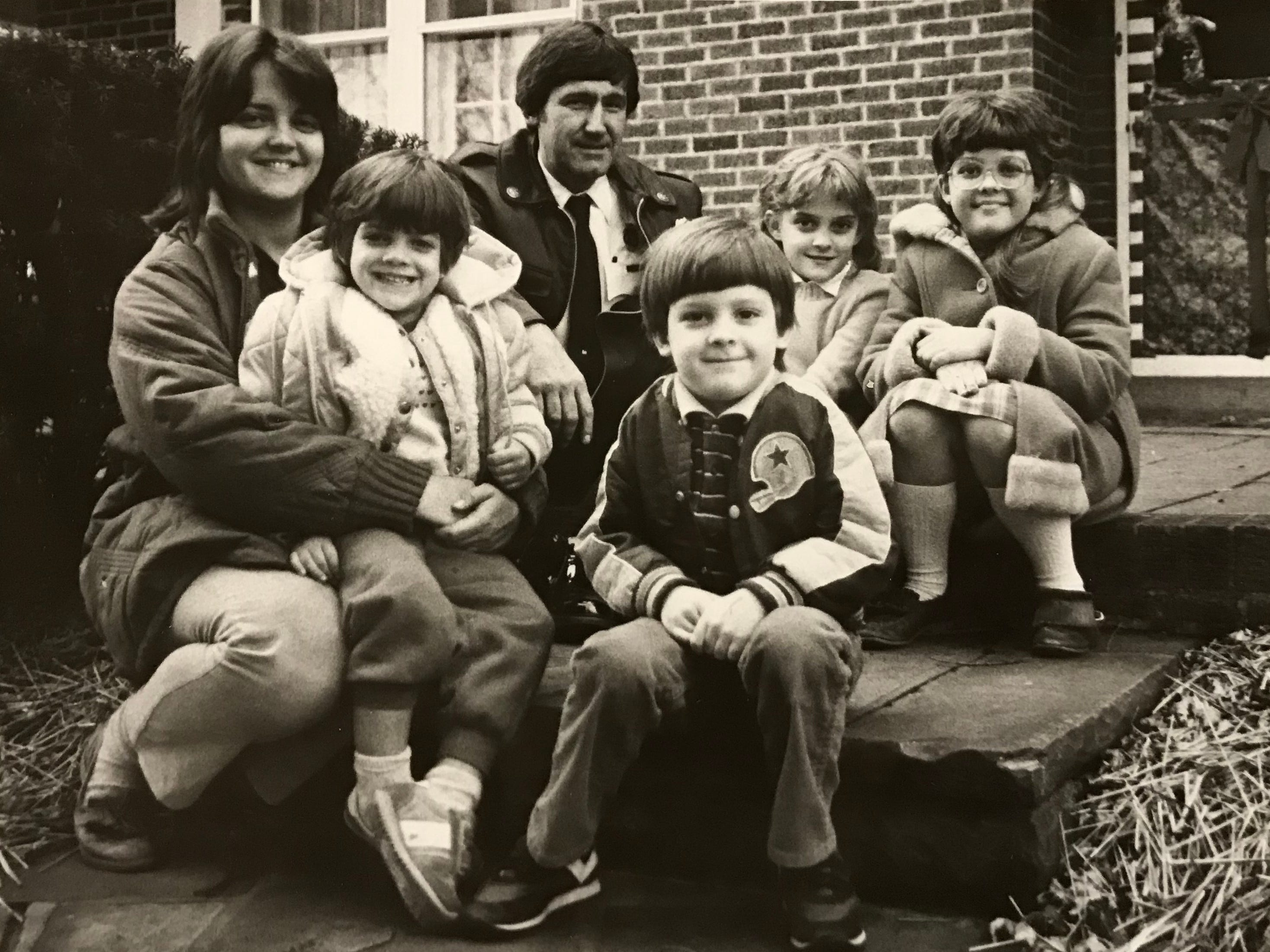 In January 1985, Jennifer Willis, far left, and her children - from left, Alison, 4, Wesley 6, Tiffany, 7, and Melissa, 9 - sit on the stop of their East Fifth Street home with Chillicothe Fire Lt. Richard Copp, background. The family received a commendation for the way they responded when their home caught fire. A smoke alarm quickly alerted Willis to the early morning fire and they put to use their fire drill plan including safety tips the kids learned at school.