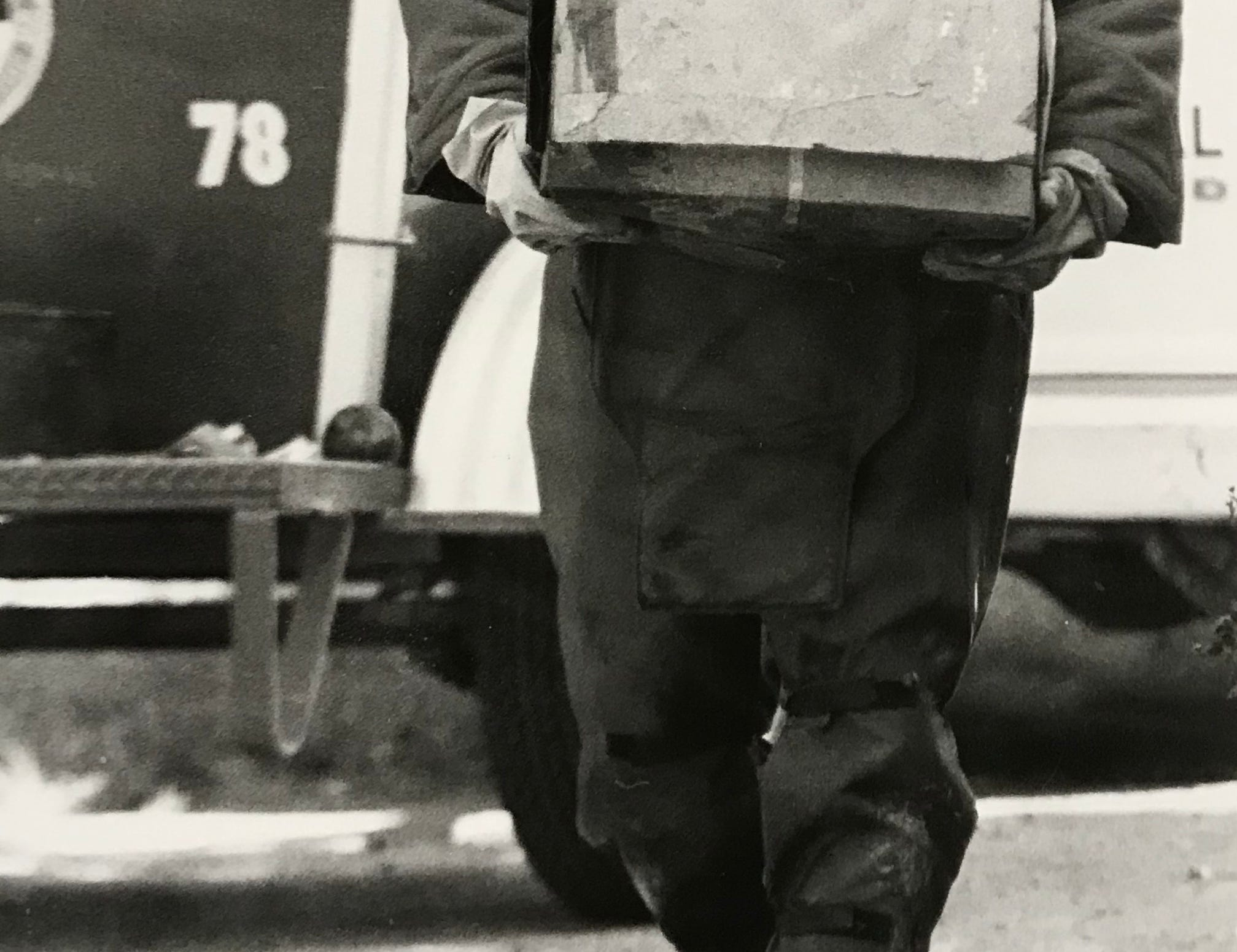 Lloyd Kaczmarek with the State Fire Marshal's hazardous materials unit removes a box of dynamite found in a mausoleum at Grandview Cemetery in September 1984.