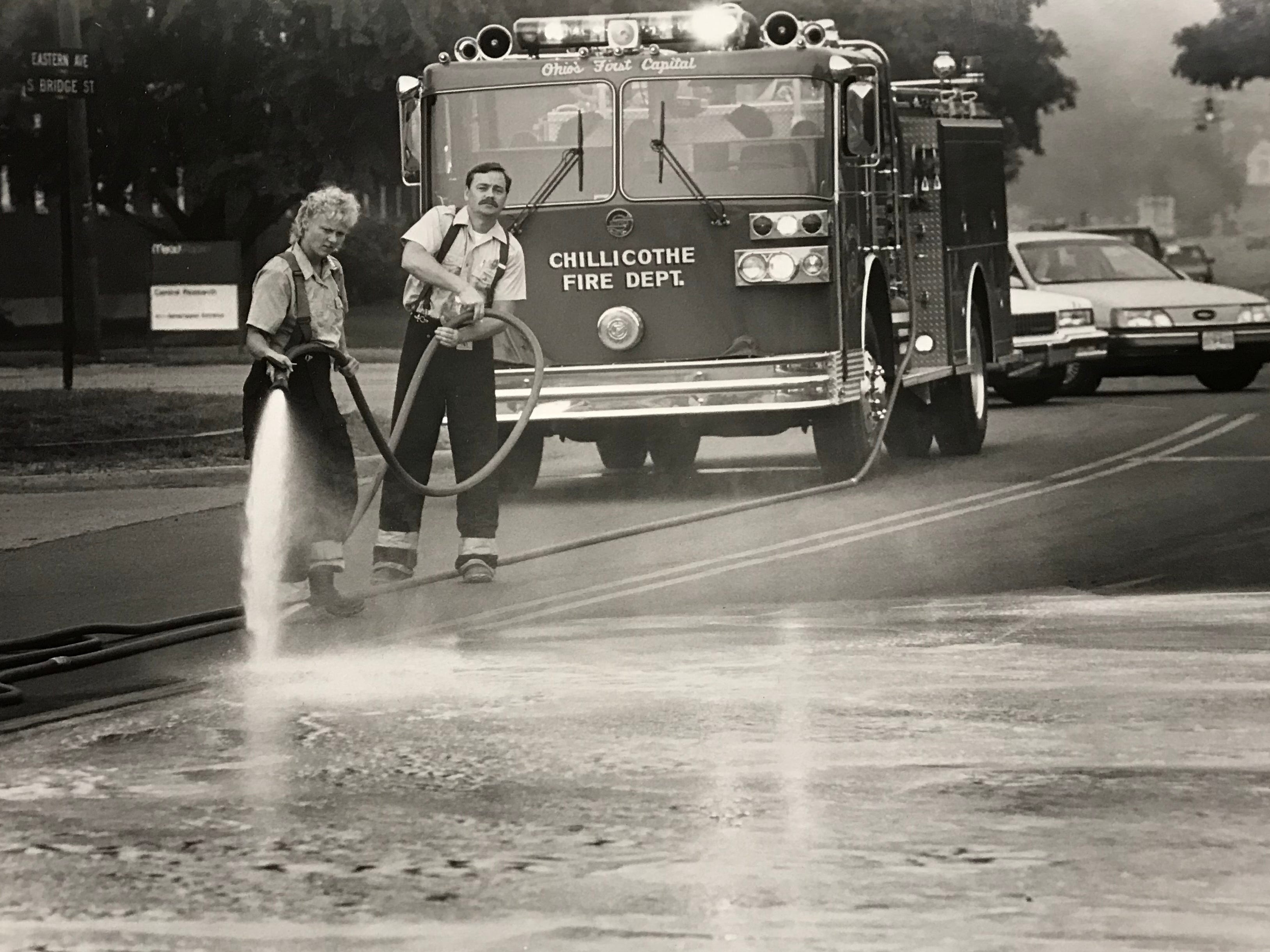 Chillicothe Firefighters Connie Unger (the department's fire female firefighter) and Brad Southwick hose down oil spilled at Bridge Street and Eastern Avenue in August 1989.