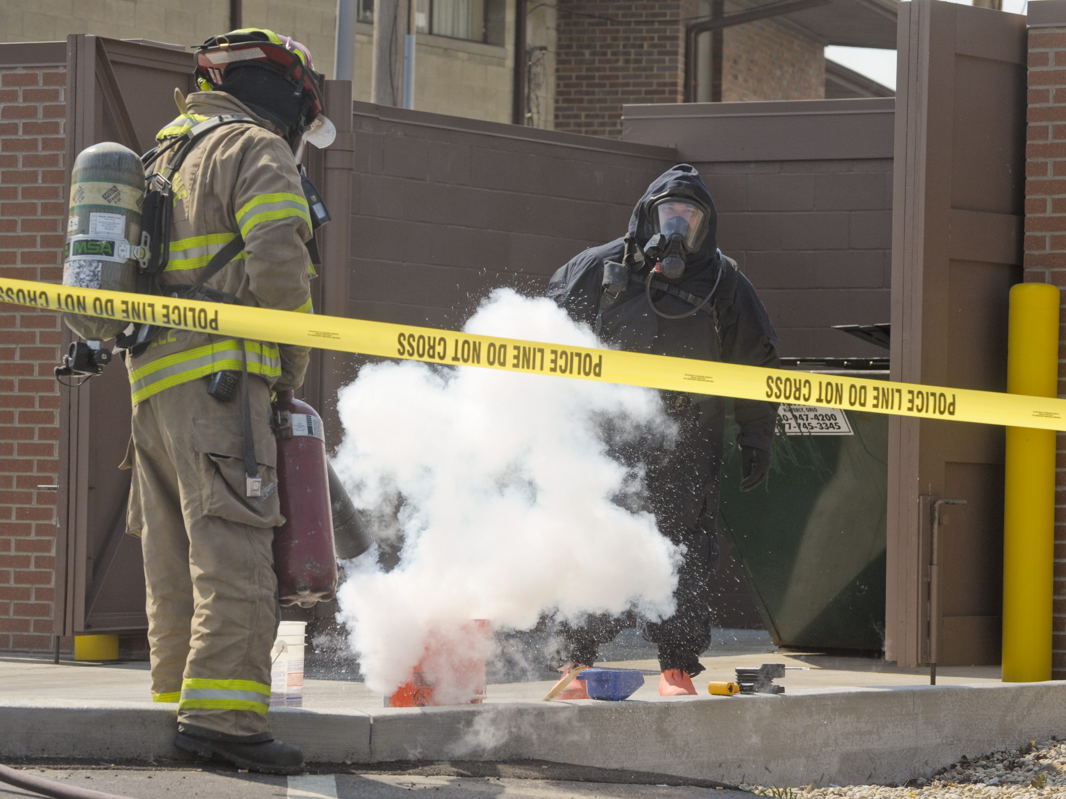 Captain Dave Russell of the Chillicothe Fire Department, left, extinguishes a small fire while BCI Agent Dennis Lowe steps back during a meth lab cleanup in June 2012.