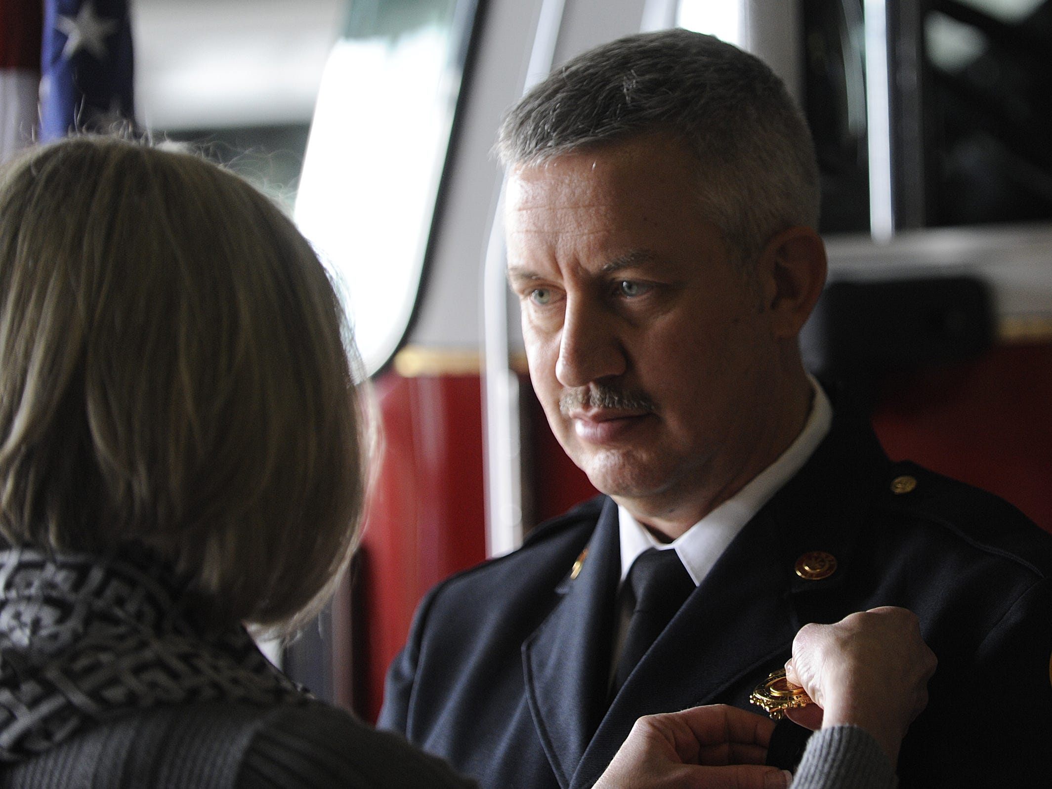 Newly named Chillicothe Fire Chief Jeff Creed waits as his wife, Chillicothe Fire Lt. Tracey Creed, pins the chief's badge on him after his swearing-in ceremony  on Jan. 25, 2013 at the Chillicothe Fire Department's Station 1.