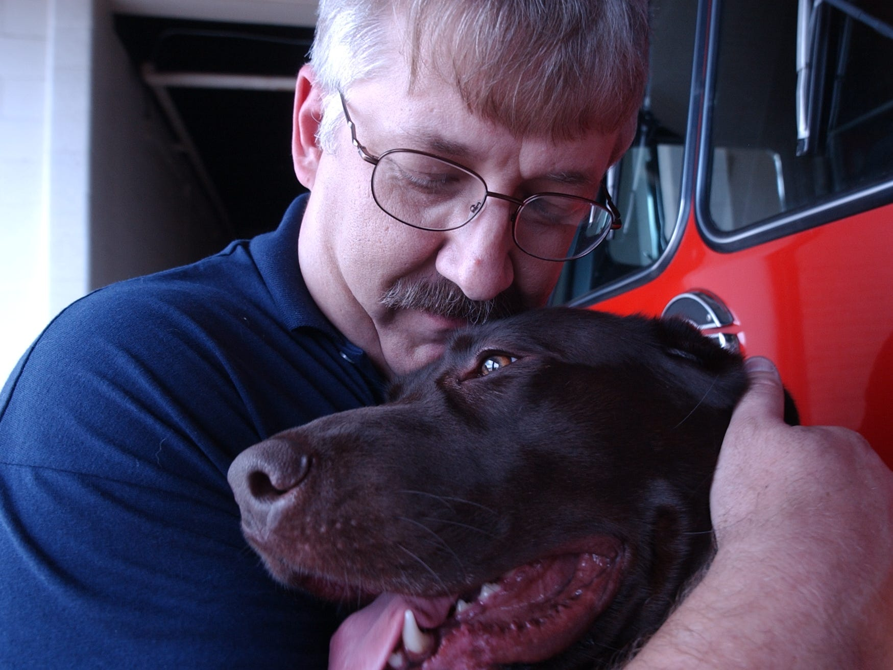 Chillicothe Asst. Fire Chief Steve Gallagher snuggles his partner, arson dog Winchester in June 2000.  Winchester died in 2011 from cancer.