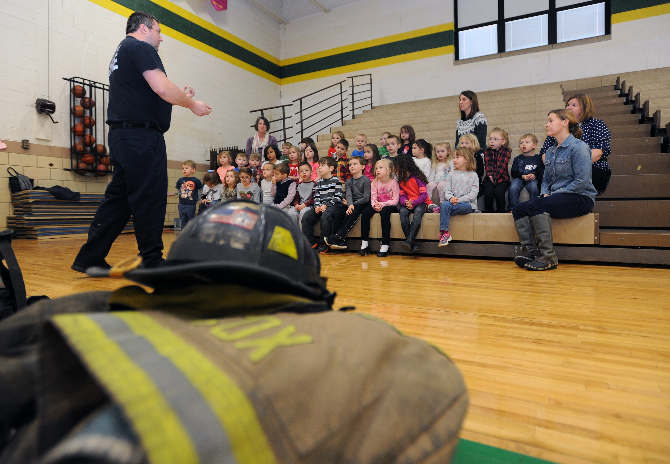 Bryan Cox, with the Chillicothe Fire Department, teaches students about his gear during a presentation Monday, Feb. 8, 2016, at Bishop Flaget Middle School. The program was put on for preschool, kindergarten and first grade classrooms by members of the Aladdin Shriners, Ross County Shrine Club and the Chillicothe Fire Department as part of ÒBe Burn AwareÓ week to educate children in the dangers of potential burn situations.