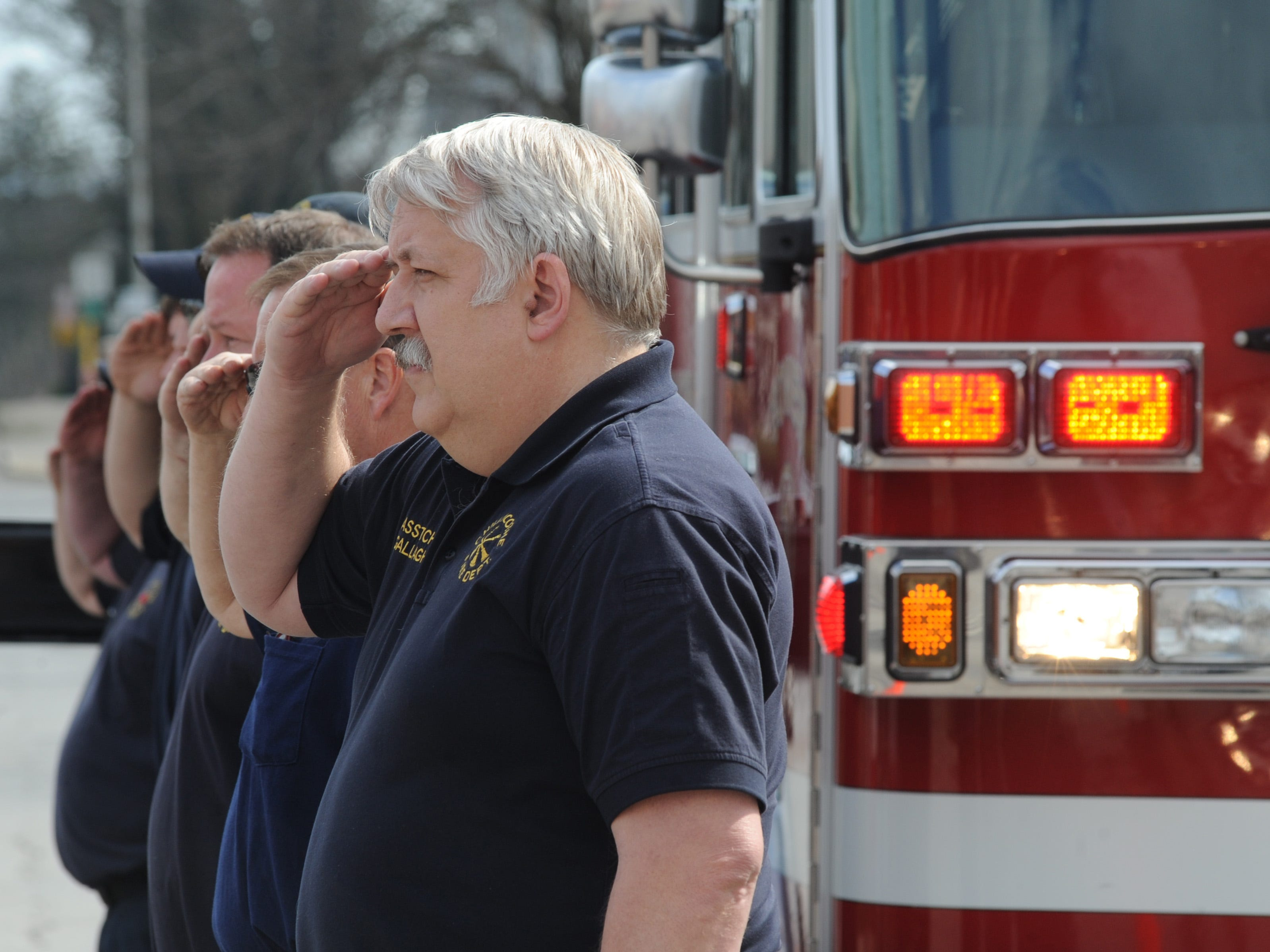 Assistant Chief Steve Gallagher stands and salutes with other Chillicothe Fire Department firefighters as the funeral procession for Cody A. King passes through the crossed ladders on Monday, March 19, 2012, in front of Fire Station 1. Frank Robertson/Gazette