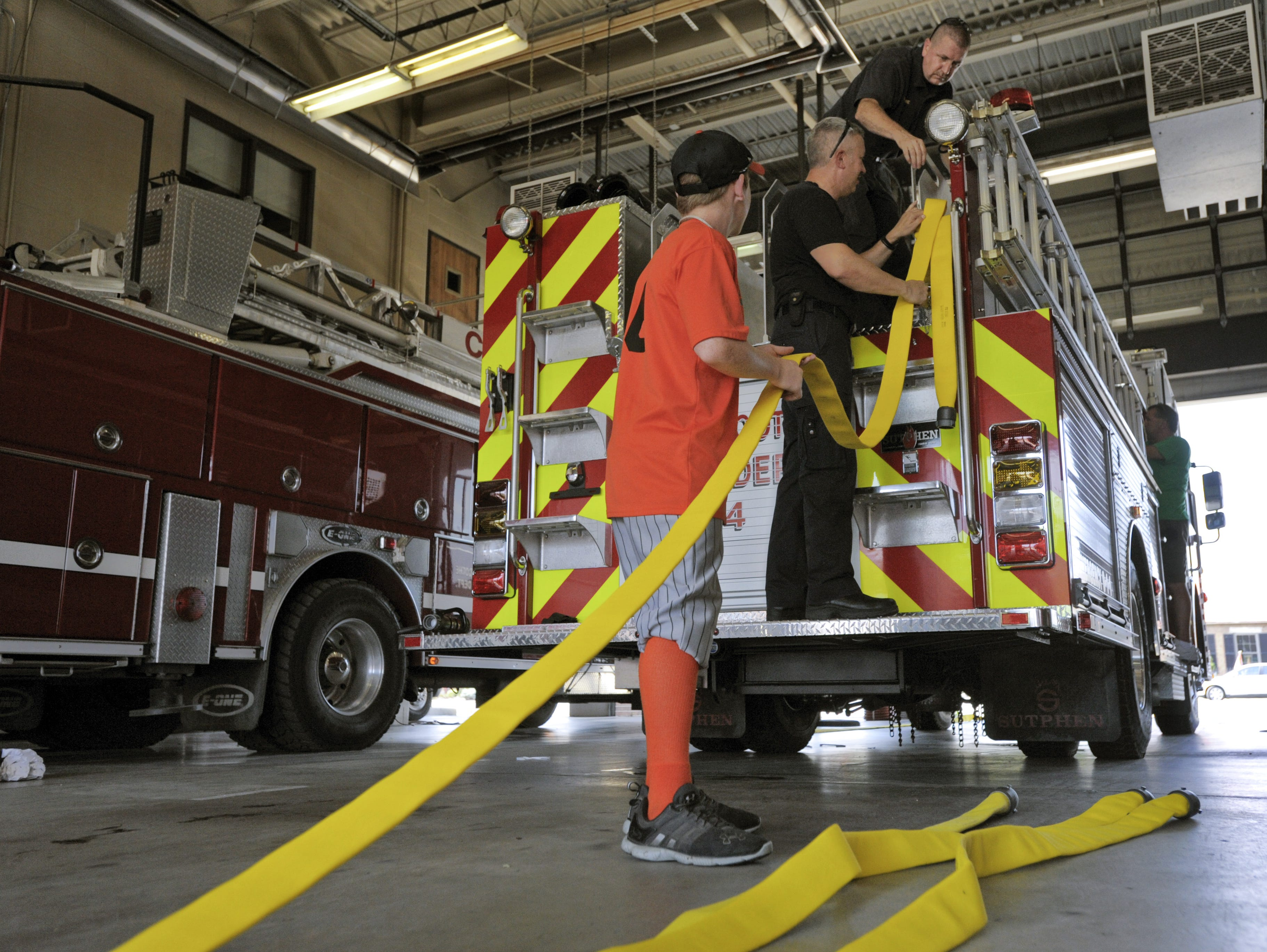 Shane Gibbs, left, helps then Interim Fire Chief Jeff Creed, center and Firefighter Tim Whitacre add fire hose to the city's new fire truck in 2012 at the Chillicothe Fire Department on East Water Street.