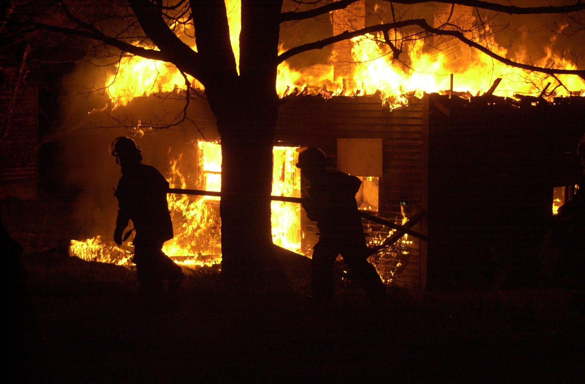Chillicothe firefighters battle a blaze of a cabin at the Country Club on April 21, 2003.