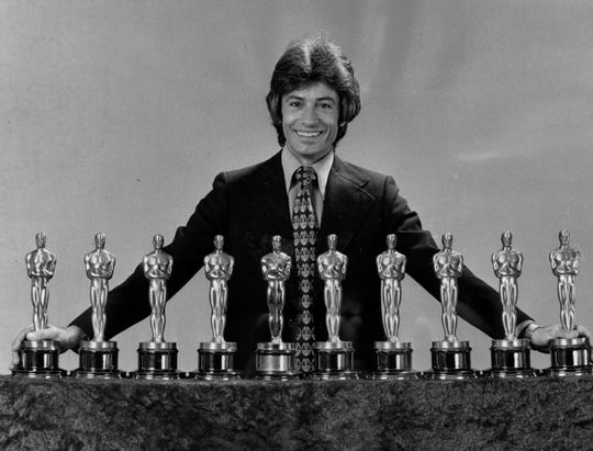 "Actor George Chakiris, from Norwood, poses with the 10 Academy Awards given to the 1961 film ""West Side Story,"" including his Oscar for supporting actor."