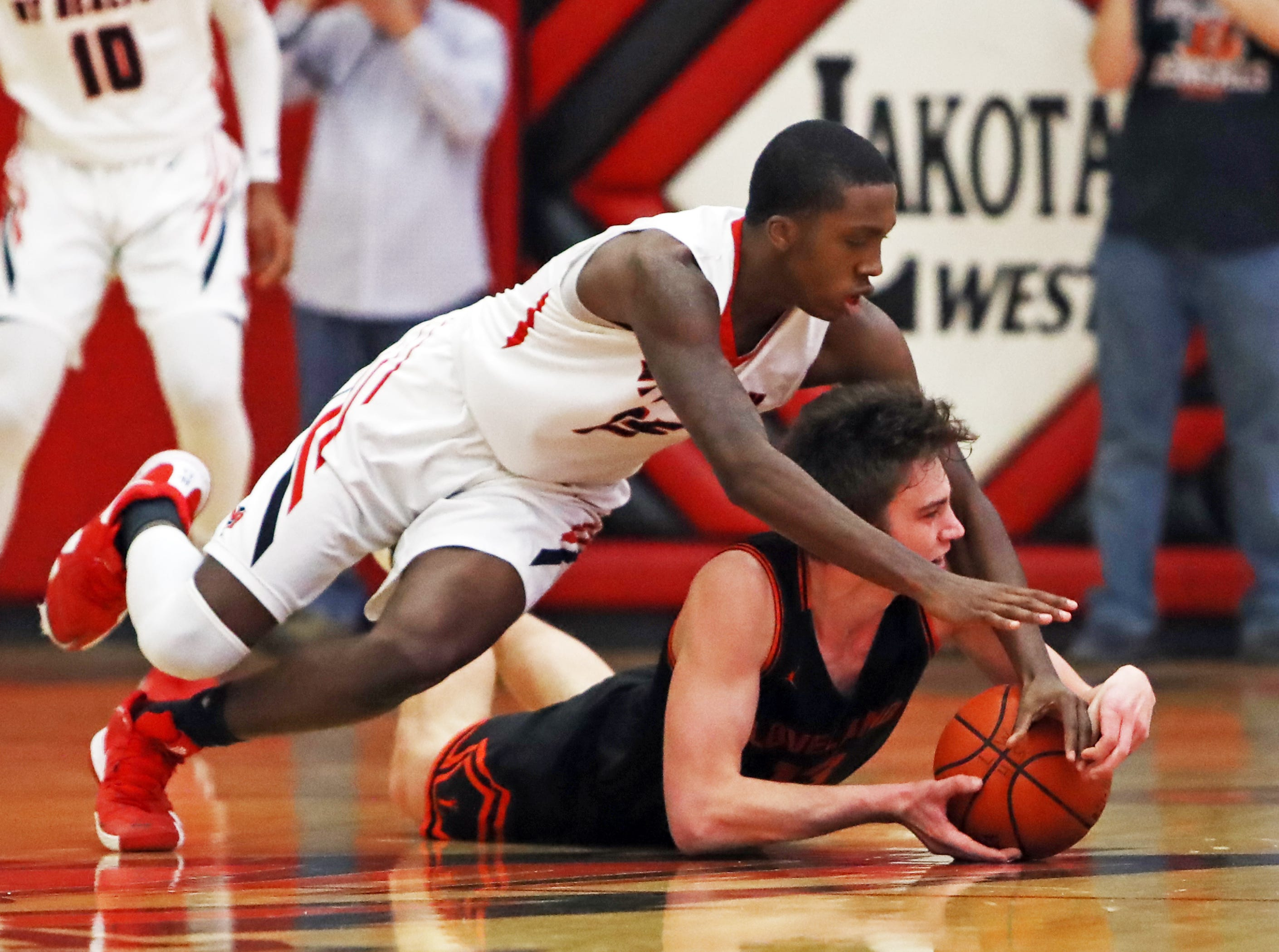 Mt. Healthy guard King Chambers and Loveland guard Jalen Greiser battle for a loose ball in the sectional playoffs at Lakota West High School Feb. 23, 2019.