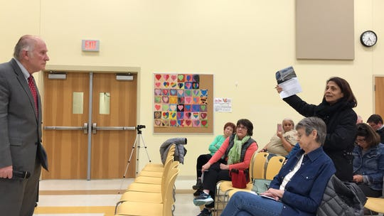 Brandishing an article on a GM plant closing, Green Township resident Rupa Townsend at a town hall Friday in Sayler Park, tells Rep. Steve Chabot(left) why she disapproves of the Republican tax plan.