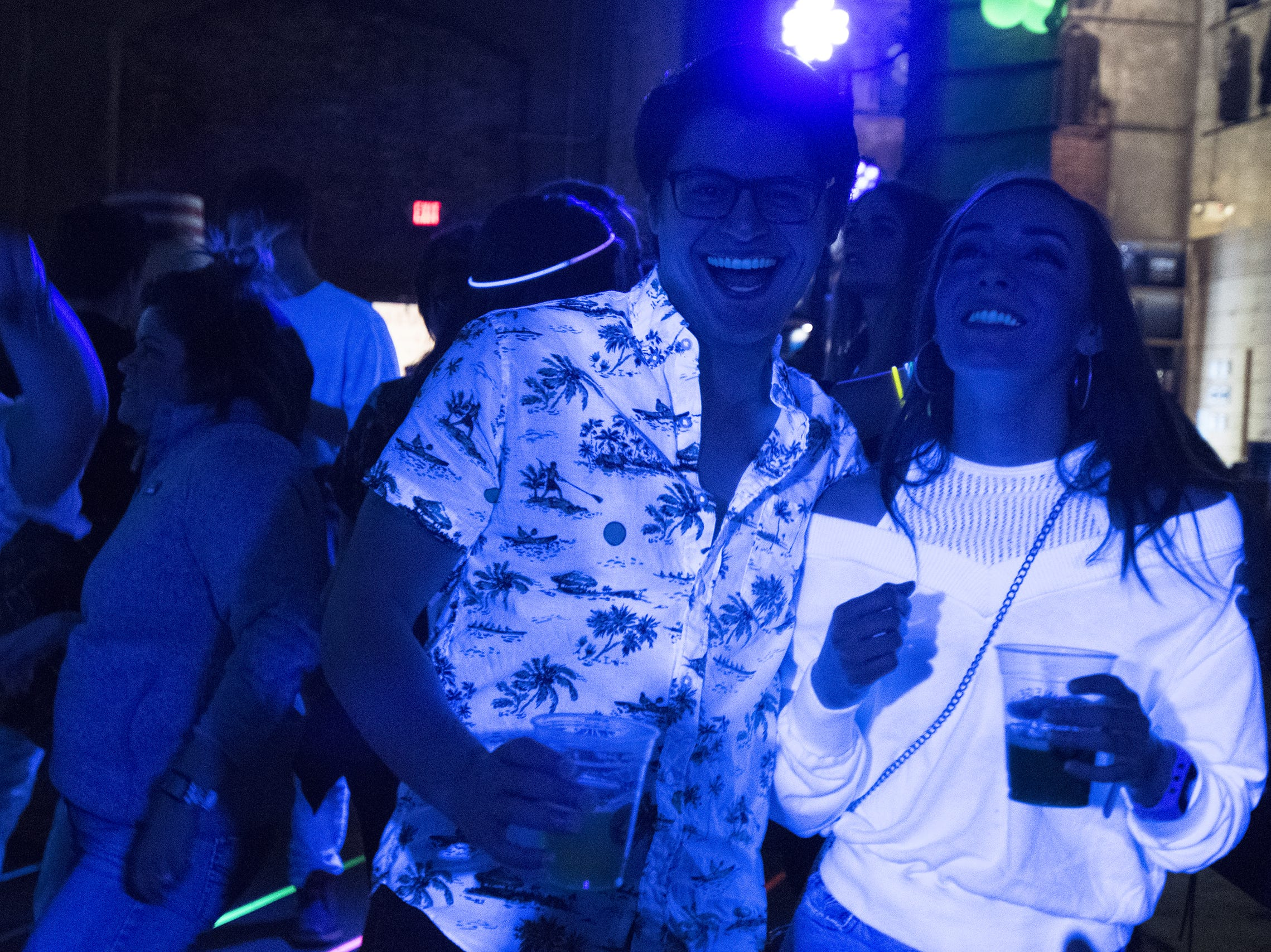Sean Sherry and Ashton Williams shine under the black lights on the dance floor at Rhinegeist's tropical disco.